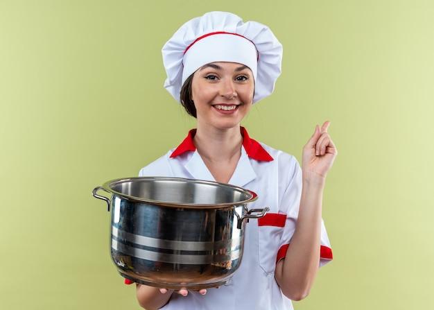Sorridente giovane cuoca che indossa l'uniforme dello chef che tiene i punti di pentola sul lato isolato su sfondo verde oliva con spazio di copia