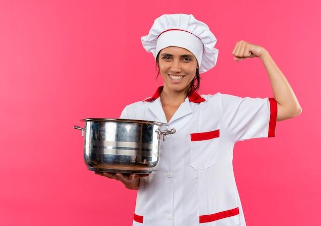 コピースペースで強いジェスチャーを示す鍋を保持しているシェフの制服を着て笑顔の若い女性料理人