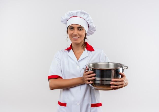 コピースペースと鍋を保持しているシェフの制服を着て笑顔の若い女性料理人