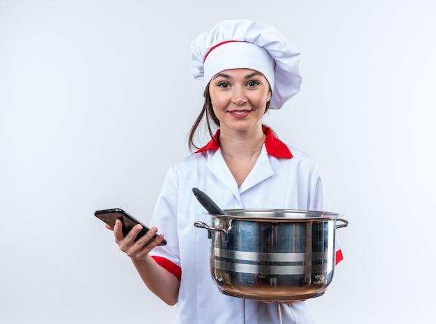 Sorridente giovane cuoca che indossa l'uniforme dello chef tenendo la casseruola con il telefono isolato su parete bianca