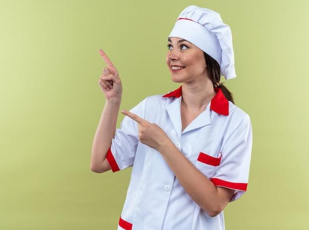 Улыбающаяся молодая женщина-повар в униформе шеф-повара с очками сбоку, изолированными на оливково-зеленой стене с копией пространства