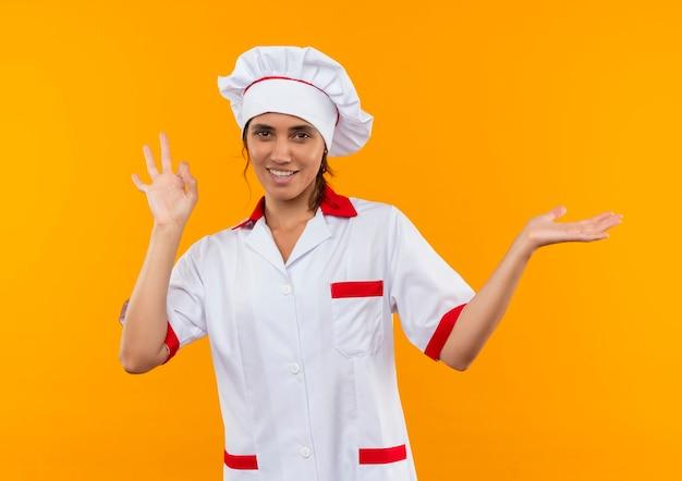 Улыбающаяся молодая женщина-повар в униформе шеф-повара показывает жест и показывает рукой в сторону с копией пространства