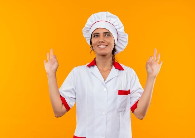 Улыбающаяся молодая женщина-повар в униформе шеф-повара показывает жест `` ок '' на изолированной желтой стене с копией пространства