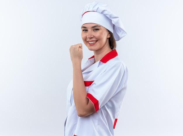 Sorridente giovane cuoca che indossa l'uniforme dello chef che mostra sì gesto isolato su sfondo bianco