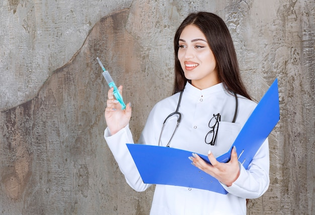 주사와 체크리스트를 들고 웃는 젊은 여성 의사