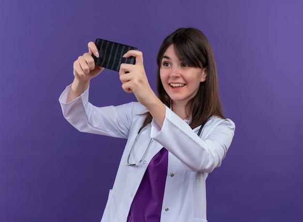 Улыбающаяся молодая женщина-врач в медицинском халате со стетоскопом держит телефон обеими руками и смотрит на телефон на изолированном фиолетовом фоне с копией пространства