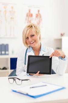 Sorridente giovane donna medico che mostra sullo schermo della tavoletta digitale