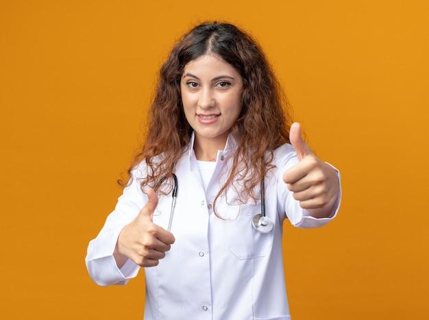 オレンジ色の壁に分離された親指を見せて正面を見て医療ローブと聴診器を身に着けている若い女性医師の笑顔