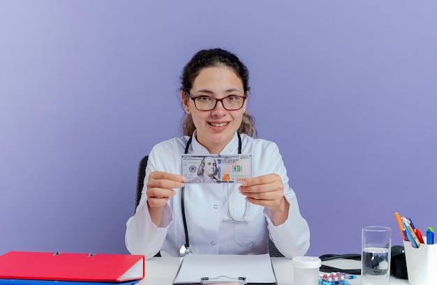 의료 가운과 격리 된 찾고 돈을 들고 의료 도구와 책상에 앉아 청진기를 입고 웃는 젊은 여성 의사