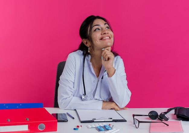 의료 가운과 청진기를 착용하는 젊은 여성 의사가 책상에 손을 얹고 분홍색 벽에 고립 된 턱 아래에서 측면을보고 의료 도구로 책상에 앉아 웃는 젊은 여성 의사