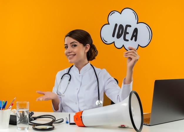 Улыбающаяся молодая женщина-врач в медицинском халате и стетоскопе сидит за столом с медицинскими инструментами, динамик и ноутбук, держа пузырь идеи, показывая пустую руку, изолированную на желтой стене