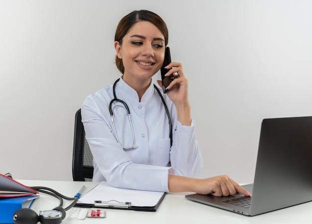 白い壁に隔離された電話で話しているラップトップを使用して、医療ツールで机に座って医療ローブと聴診器を身に着けている若い女性医師の笑顔