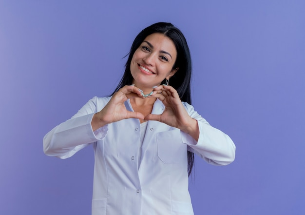 Smiling young female doctor wearing medical robe doing heart sign isolated on purple wall with copy space