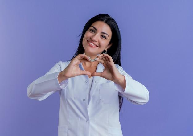 Sorridente giovane medico femminile che indossa abito medico facendo segno di cuore isolato sulla parete viola con spazio di copia
