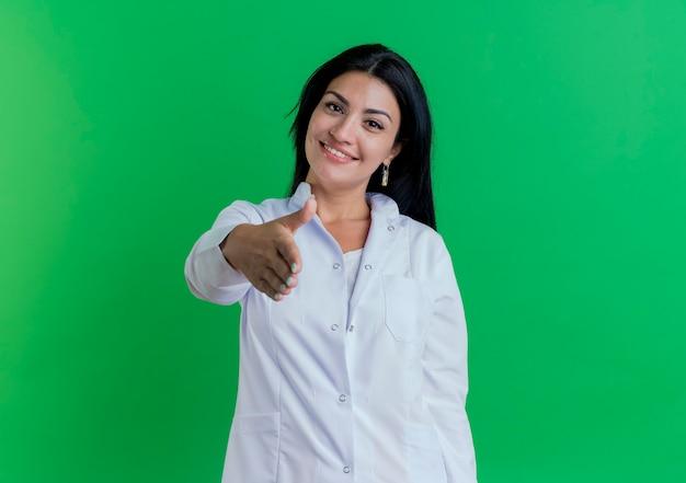 Giovane medico femminile sorridente che porta veste medica che fa ciao gesto che saluta qualcuno isolato sulla parete verde con lo spazio della copia