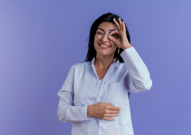 Sorridente giovane medico femminile che indossa abito medico che fa gesto di sguardo mettendo la mano sulla pancia isolata sulla parete viola con lo spazio della copia