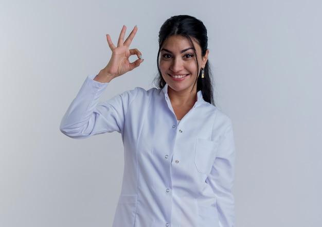 Sorridente giovane medico femminile che indossa abito medico facendo segno ok guardando isolato