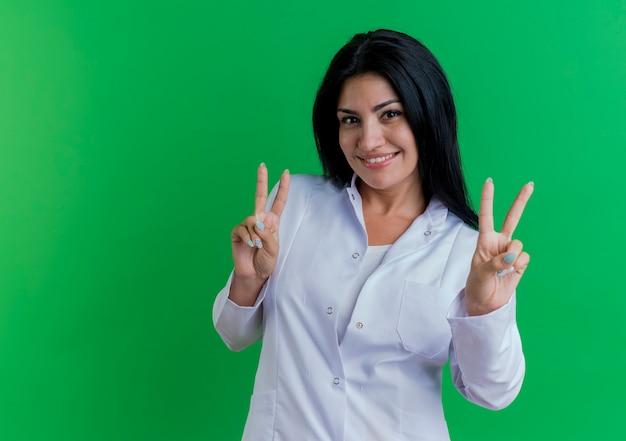 복사 공간 녹색 벽에 고립 된 평화 서명 하 고 의료 가운을 입고 웃는 젊은 여성 의사