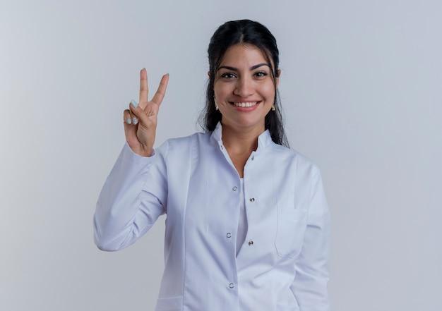 복사 공간 흰 벽에 고립 된 평화 서명 하 고 의료 가운을 입고 웃는 젊은 여성 의사