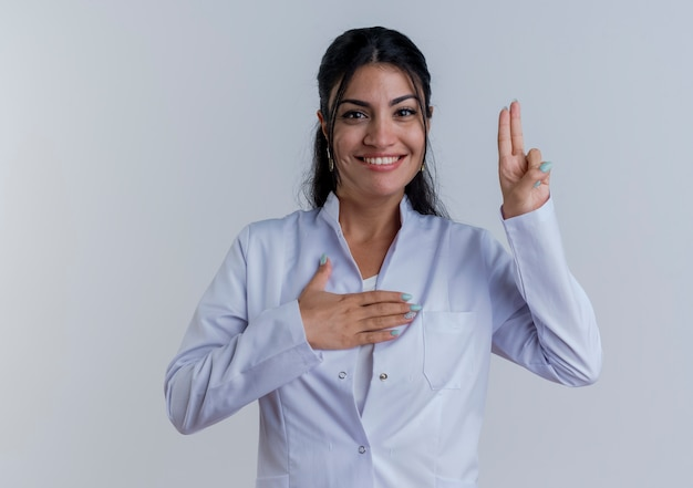 Smiling young female doctor wearing medical robe  doing promise gesture isolated on white wall with copy space