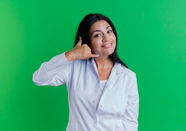 Sorridente giovane donna medico indossa abito medico guardando facendo gesto di chiamata