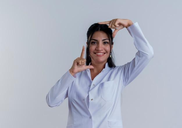 Sorridente giovane medico femminile che indossa abito medico cercando di fare il gesto del telaio isolato