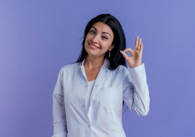 Sorridente giovane medico femminile che indossa abito medico guardando facendo segno ok