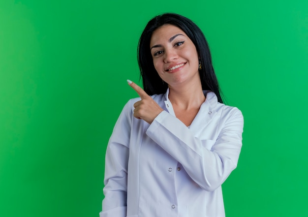 측면에서 가리키는 찾고 의료 가운을 입고 웃는 젊은 여성 의사