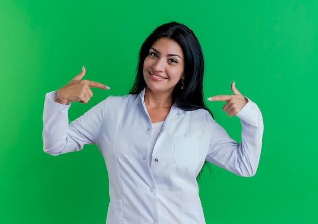 Sorridente giovane donna medico indossa abito medico guardando e indicando se stessa