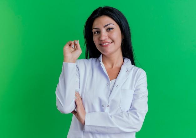 의료 가운을 입고 웃는 젊은 여성 의사가 공중에 또 하나를 유지하는 팔에 손을 넣어보고