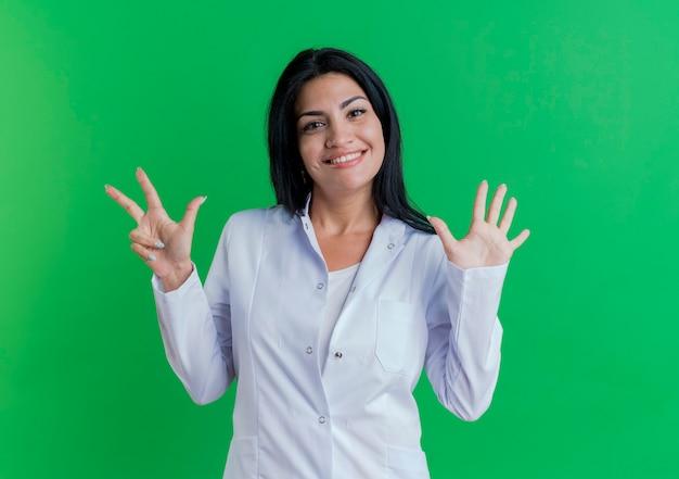 手で8を示している医療ローブを身に着けている若い女性医師の笑顔