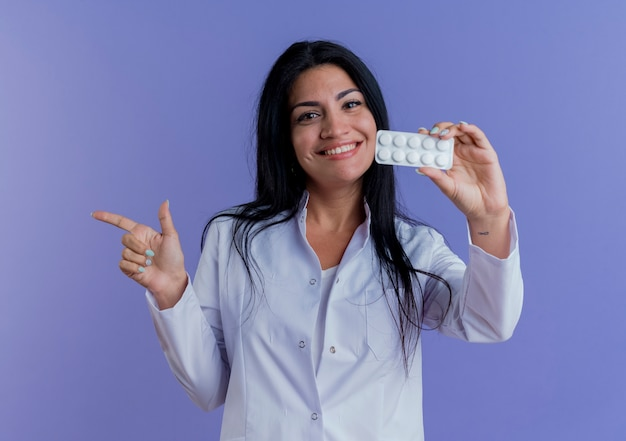 Sorridente giovane dottoressa indossa abito medico che mostra confezione di compresse medicali, guardando rivolto a lato