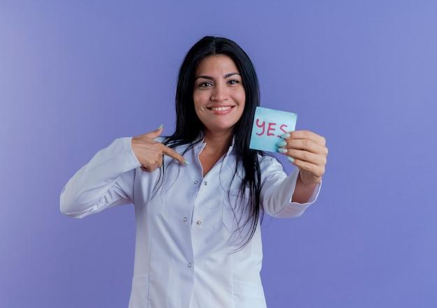 예 참고를 보여주는 의료 가운을 입고 웃는 젊은 여성 의사, 자신을 가리키는 찾고