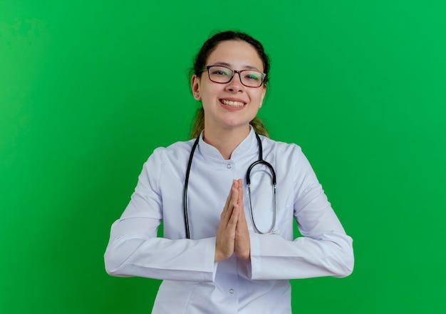 Sorridente giovane medico femminile che indossa abito medico e stetoscopio e bicchieri tenendo le mani insieme isolato sulla parete verde con lo spazio della copia
