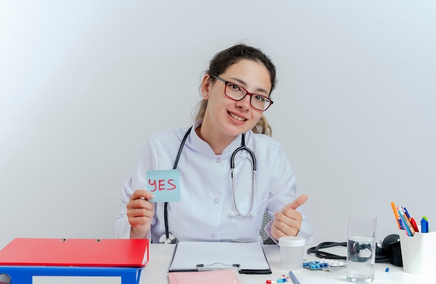 Sorridente giovane dottoressa indossa veste medica e stetoscopio e occhiali seduto alla scrivania con strumenti medici guardando tenendo sì nota che mostra il pollice in alto isolato