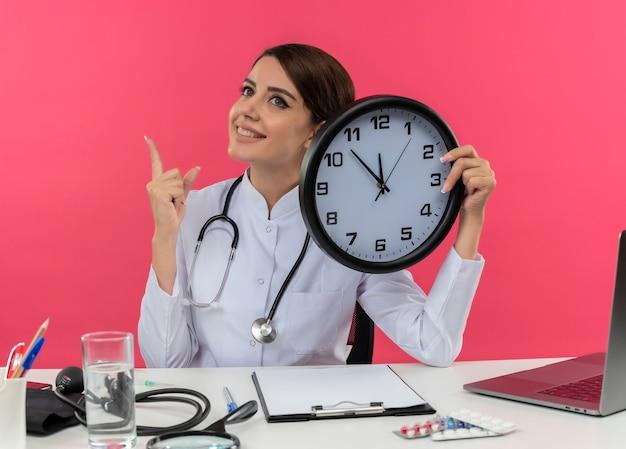Sorridente giovane medico femminile che indossa abito medico e stetoscopio seduto alla scrivania con strumenti medici e laptop tenendo l'orologio alla ricerca e rivolto verso l'alto isolato sul muro rosa