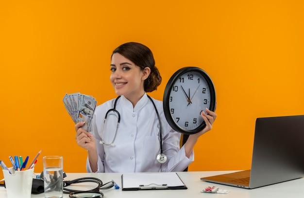 Sorridente giovane medico femminile che indossa abito medico e stetoscopio seduto alla scrivania con strumenti medici e computer portatile che tiene orologio e soldi isolati sulla parete gialla