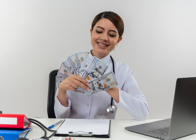 Smiling young female doctor wearing medical robe and stethoscope sitting at desk with medical tools and laptop holding and looking at money isolated on white wall