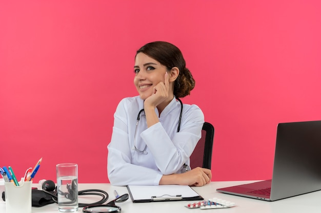 Sorridente giovane medico femminile che indossa abito medico e stetoscopio seduto alla scrivania con strumenti medici e computer portatile che mette le mani sulla scrivania e sul mento guardando dritto isolato sul muro rosa