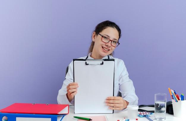 Sorridente giovane medico femminile che indossa abito medico e stetoscopio seduto alla scrivania con strumenti medici cercando mostrando appunti isolati