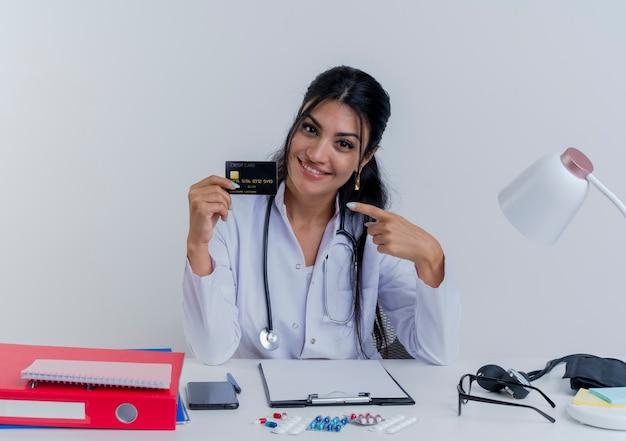 Sorridente giovane medico femminile che indossa abito medico e stetoscopio seduto alla scrivania con strumenti medici cercando di mostrare la carta di credito che punta a esso isolato
