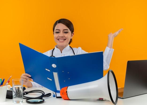 Sorridente giovane medico femminile che indossa veste medica e stetoscopio seduto alla scrivania con strumenti medici altoparlante e laptop tenendo e guardando la cartella che mostra la mano vuota isolata sul muro giallo