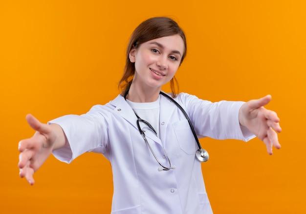 Sorridente giovane medico femminile che indossa abito medico e stetoscopio che allunga le mani sulla parete arancione isolata