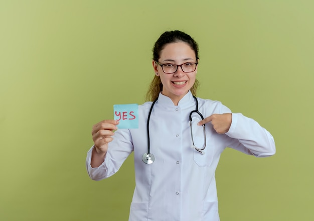 Sorridente giovane medico femminile che indossa abito medico e stetoscopio con i vetri che tengono i punti di nota di carta a se stessa isolati sulla parete verde oliva