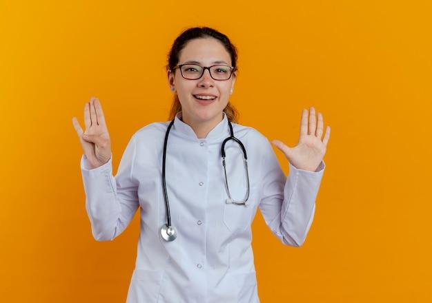 Sorridente giovane medico femminile che indossa abito medico e stetoscopio con gli occhiali che mostrano numeri differenti isolati sulla parete arancione