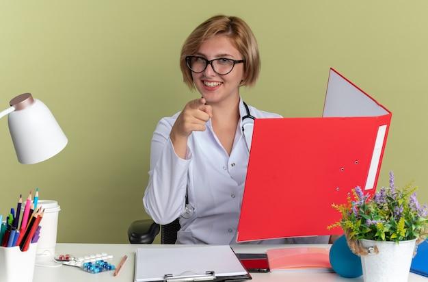 안경과 청진기가 달린 의료 가운을 입은 웃고 있는 젊은 여성 의사는 올리브 녹색 배경에 격리된 카메라를 가리키고 폴더를 들고 있는 의료 도구와 함께 테이블에 앉아 있습니다.