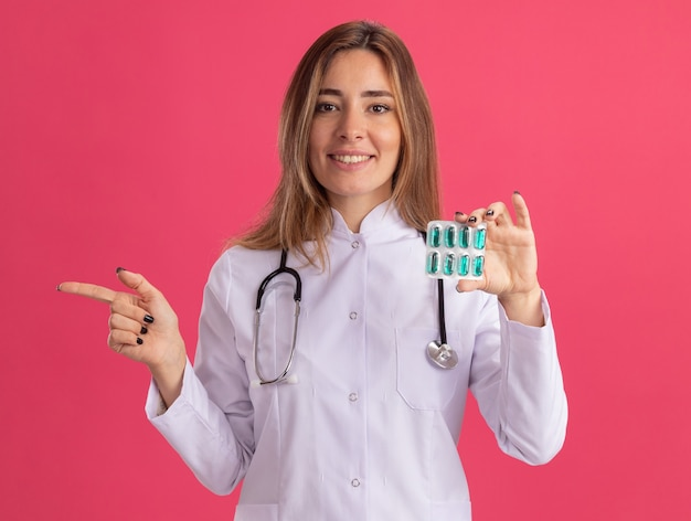 청진 기 핑크 벽에 고립 된 측면에서 약 포인트를 들고 의료 가운을 입고 웃는 젊은 여성 의사