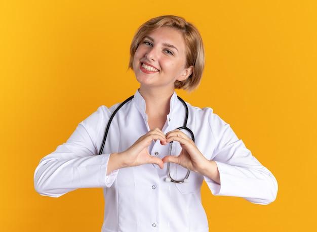 オレンジ色の背景に分離された心臓のジェスチャーを示す聴診器と医療ローブを着て笑顔の若い女性医師