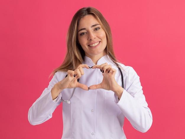 Sorridente giovane medico femminile indossa abito medico con lo stetoscopio che mostra il gesto del cuore isolato sulla parete rosa