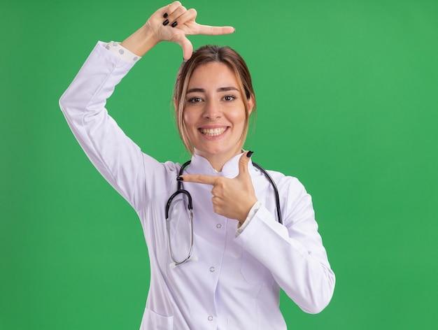 Sorridente giovane medico femminile che indossa abito medico con lo stetoscopio che mostra il gesto della foto isolato sulla parete verde